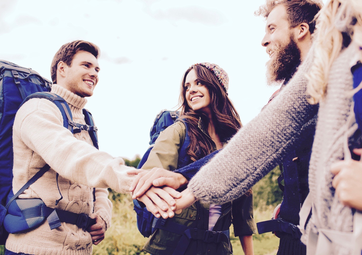 travel, tourism, hike, gesture and people concept - group of smiling friends with backpacks putting hands on top of each other